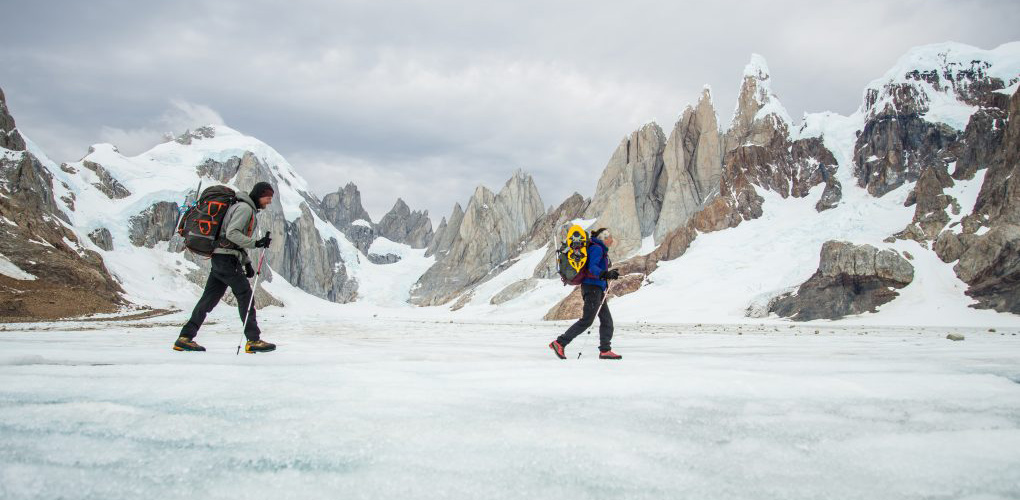 The author and partner, Brinannala Morgan walk across the meltwater pools on the surface of the Campo de Heilo Norte with the Torres and the Circo de los Altares in the background.