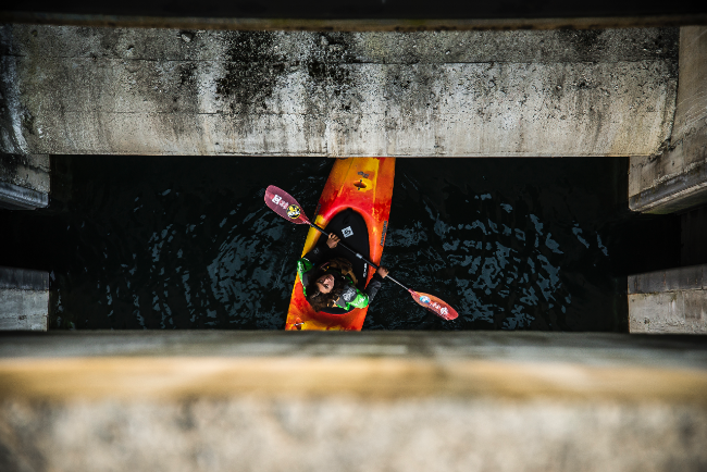 Canela Astorga kayaking below a bridge. Photo: Erick Vigoroux