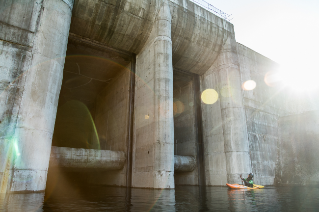 The kayakers in front of a dam. Photo: Carlos Lastra